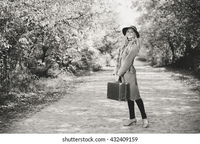 Black and white portrait of woman alone with vintage suitcase hitchhiking on empty road outdoors. Travel abroad