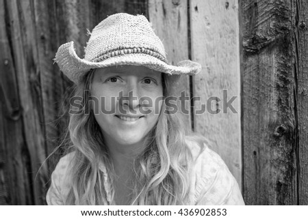 Black and white portrait of a woman wearing a cowboy hat with a barn wood  background 2c74adc3d9f9
