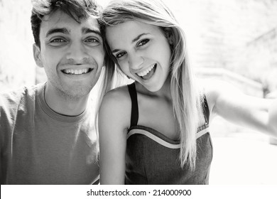 Black and white portrait of a young attractive tourist couple using a smartphone to take a selfie picture of themselves on holiday while visiting a touristic destination city, having fun outdoors.