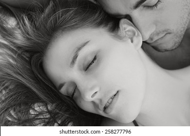 Black and white portrait of young attractive romantic couple hugging and kissing, laying down on a bed, having sex and being loving with each other. Love and relationships lifestyle, interior bedroom.