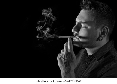 Black and white portrait of young, attractive man, with ear tunnel and facial hair smoking a cigarette