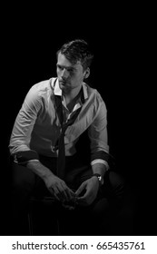 Black and white portrait of young, attractive man in unbuttoned, creased white shirt with rolled up sleeves and loose tie sitting in the dark