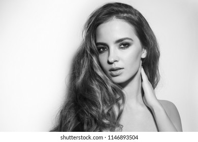 Black and white portrait of young beautiful woman with long messy curly hair