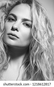 Black and white portrait of young beautiful woman with messy curly hair