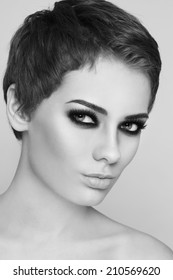 Black and white portrait of young beautiful woman with stylish short haircut and smoky eyes