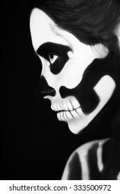 Black and white portrait of young beautiful woman with skeleton face art makeup, black background.