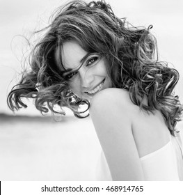 Black and white portrait of a young beautiful woman. Woman in Black & White. Black and white portrait of smile woman. Close-up. Black white photography.  Summer portrait on the beach, sea, ocean