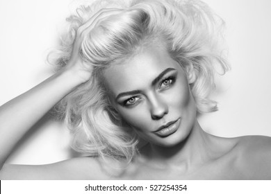 Black and white portrait of young beautiful glamorous woman with messy platinum blonde hair