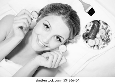 Black and white portrait of young beautiful attractive girl blond woman lying with slices of cucumber on eyes and happy smiling