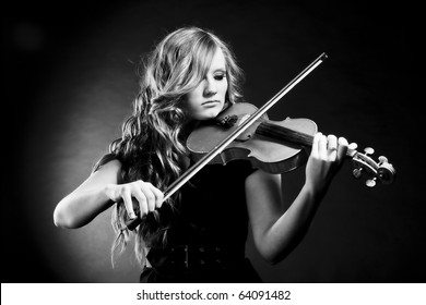 Black and white portrait of young, beautiful violinist playing her violin