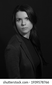 Black and white portrait of a young brunette woman in a studio on a black background