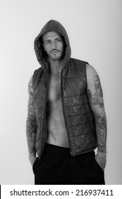 Black and white portrait of Young brunette shirtless male model wearing a vest