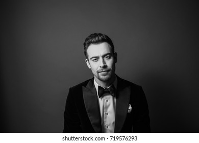 Black and white portrait of a young business in a suit, white shirt and bow tie, serious and looking straight at the camera, against plain studio background.