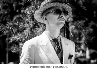 Black and white portrait of a young dandy wearing a tie, a pocket handkerchief and a straw boater hat, in front of greeneries