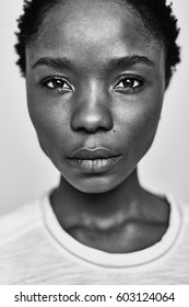 Black and white portrait of a young dark-skinned woman with a short stitch, on a white background