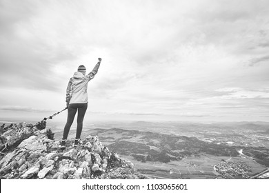 Black and white portrait of young female hiker with trekking poles and arm raised celebrating achievement standing on top of mountain after successful ascent - adventure, freedom or success concept