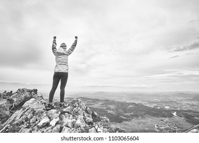 Black and white portrait of young female hiker with arms raised celebrating achievement standing on top of mountain after successful ascent - adventure, freedom or success concept