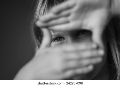 black and white portrait of young girl looking through hand as a director and cameraman