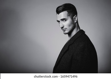 Black and white portrait of young and handsome model in a classic black jacket. Studio shot. Copy space.