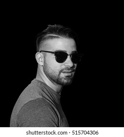 Black and white portrait of young handsome man in sunglasses - Black in the background - Close up portrait of a beautiful man