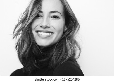 Black and white portrait of young happy woman with a big smile on her face