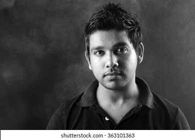 Black and white portrait of a young Indian against a smoky background.With harsh light and shadow treatment.