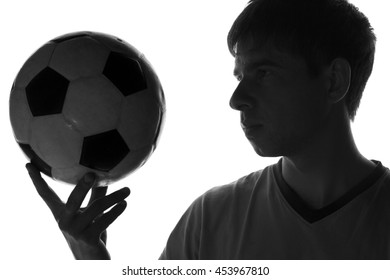 black and white portrait of a young man with a soccer ball in his hand