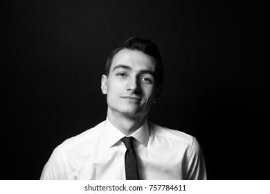 Black and white portrait of a young man in a shirt and black tie, looking at the camera, against plain studio background