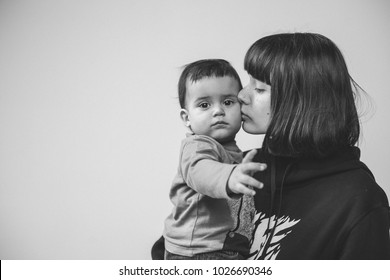 Black and white portrait of young mother who is kissing her son, toddler with serious sad expression, lots of place for text