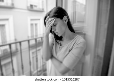 black and white portrait young sad desperate hispanic girl at home balcony looking depressed suffering terrible migraine headache disorder or depression feeling hopeless in life problems concept
