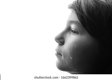 Black and white portrait of young sad boy crying with sad eyes. White background. Free space for text. Tear on cheek of unhappy teenager.