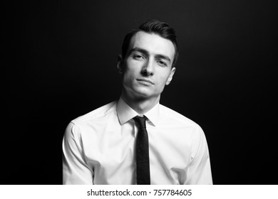 Black and white portrait of a young self-confident man in a shirt and black tie, looking at the camera, against plain studio background