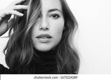 Black and white portrait of a young serious woman looking directly in camera