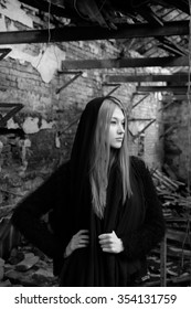 Black and white portrait of young woman, with long blond hair, wearing on black jacket with scarf on her head, posing on the destroyed old building background, waist up