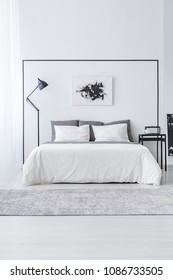Black and white poster above bed between table and lamp in simple bedroom interior