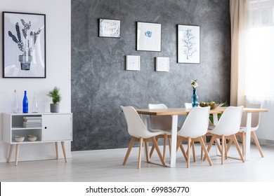 Black and white poster on white wall above white cupboard in classic dining room