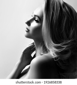 Black and white profile portrait of young pretty sexy blonde woman holding neck looking aside Black and white image. Beautiful woman, fashion, style concept