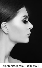 Black and white profile portrait of young beautiful woman with extended eyelashes