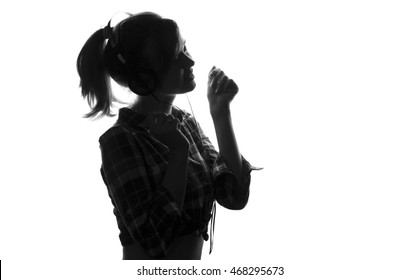 Black and white profile of a young girl listening to music on headphones and sings