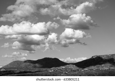 Black and white Puffy white clouds hovering over the Catalina Mountains in the Tucson, Arizona desert