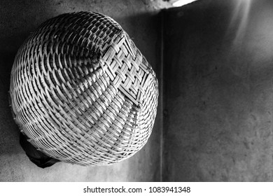 A black and white, push process filtered view of a handwoven spherical basket hanging against the corner of a shadowed interior wall.
