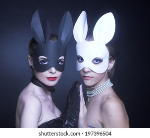 Black and white rabbits. Two young women in masks.