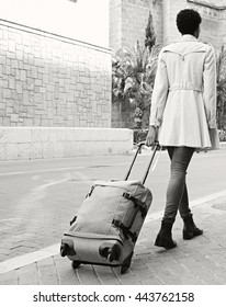Black and white rear view of elegant professional woman walking in a classic city street dragging a luggage suitcase, outdoors. Tourist holiday with bag in destination town exterior, lifestyle.