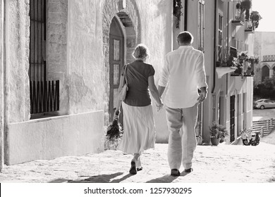 Black and white rear view of mature tourist couple walking together holding hands and bouquet, sightseeing on retirement activities holiday outdoors. Senior people vacation, travel leisure lifestyle.