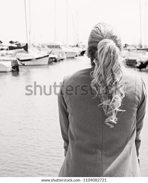 Black and white rear view of a young woman solo traveller tourist visiting destination port, contemplating sunny outdoors. Female on holiday, calm and relaxing, leisure recreation travel lifestyle.