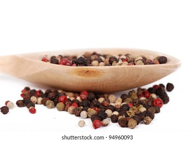 black, white and red pepper spice on wooden spoon over white background/ground pepper
