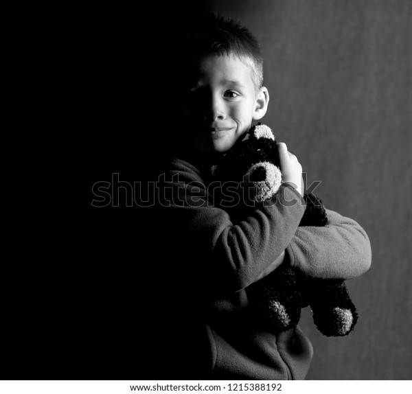 Black and white rendered image of a boy holding his teddy bear with a shadow covering half his face.