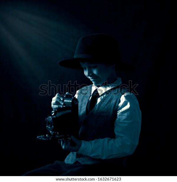 Black and white rendered image of a young boy holding an antique, retro camera.