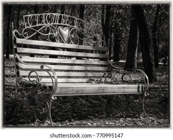 Black and white retro vintage look of a wooden and metal bench is located in a park way. It is autumn season and leaves are falling to the ground. Fall mood. With the enscryption - There is happiness.