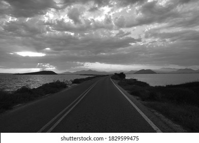 black and white road near the sea under gorgeous sky
